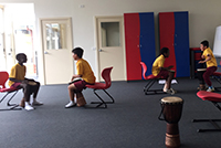 Children playing drums in the Holyoake Drumbeat program